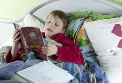 in bed with the flu doing schoolwork - stock photo