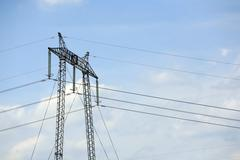 High Voltage Electrical Pylon Against Clear Blue Sky - stock photo