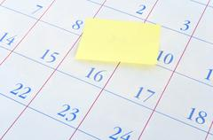 Yellow memo note on a calendar - stock photo
