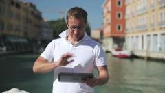 Rich man with tablet computer chatting in Venice Stock Footage