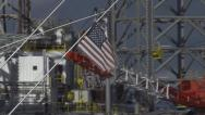 Stock Video Footage of Faded Tattered US Flag Passing Oil & Gas Rig at Harbor
