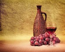 Artistic arrangement of bottles of wine and grapes Stock Photos