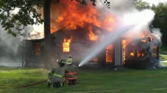 Amid the Force of Nature - Firemen Fight a House Fire with a High Pressure Hose - stock footage
