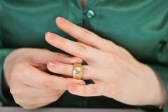 woman tries on large gold ring - stock photo