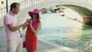 Happy rich couple standing with cellphone on the street in Venice Stock Footage