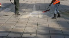 Workers cleaning city square  pavement Stock Footage