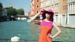Rich woman in hat standing on the bridge in Venice Stock Footage