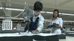 Asian Garment Industry Factory: Worker cuts with Supervisor Nearby - stock footage