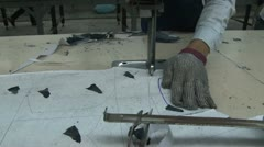 Asian Garment Industry Factory: CU metallic glove while worker cuts fabric Stock Footage