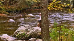 Man fly fishing mountain autumn stream Stock Footage