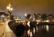 Stock Photo of bridge over the amstel river at night in amsterdam