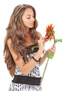 young beautiful girl with long hairs holding sunflower on white - stock photo