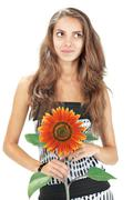 Stock Photo of young beautiful girl with long hairs holding sunflower on white