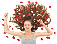 Stock Photo of young beautiful brunette woman with scattered long hairs and rose petals