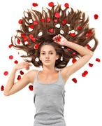 young beautiful brunette woman with scattered long hairs and rose petals - stock photo