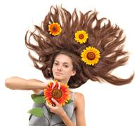 Stock Photo of young beautiful brunette woman with scattered long hairs and sunflower