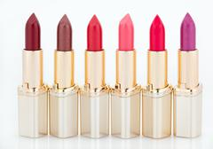 Multicolored color lipsticks arranged in line isolated on white Stock Photos