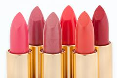 Multicolored color lipsticks arranged in two lines isolated on white, shallow Stock Photos