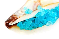 Sea shell with blue dead sea salt isolated on white Stock Photos