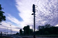 Semaphore on railway station in front of dramatic fleecy clouds sky Stock Photos