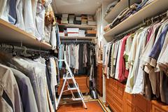 Wardrobe with many clothes and step-ladder Stock Photos