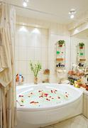 Modern bathroom in warm tones with jacuzzi and rose petals wide angle view Stock Photos