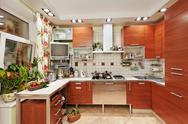 Stock Photo of kitchen interior with wooden furniture and many utensils