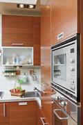 Part of kitchen interior with wooden furniture and build in microwave oven Stock Photos