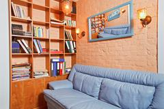 Part of cabinet interior with wooden shelving and blue leather couch Stock Photos