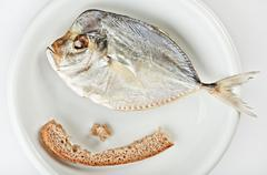 Salted moonfish with crust of bread on white plate Stock Photos