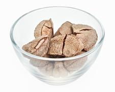 brazil nuts in a glass bowl isolated on white - stock photo
