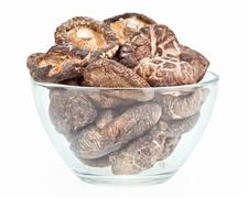 Dried field mushrooms in a glass bowl isolated on white Stock Photos