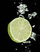 lime (lemon)  falling in water on black - stock photo