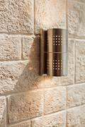 Modern metal lamp on ashlar wall pattern Stock Photos