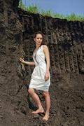 lady in white sundress inside a deep black ground quarry - stock photo