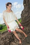 barefooted attractive lady in white on soil quarry - stock photo