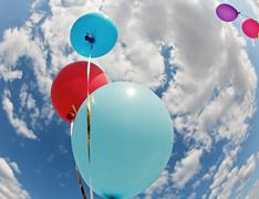 Three vivid color balloons on blue sky background Stock Photos