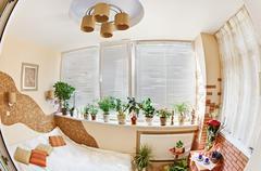 Sunny bedroom on balcony with window and plants, fisheye view Stock Photos