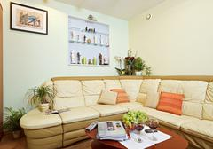 part of drawing-room interior with beige corner leather sofa - stock photo
