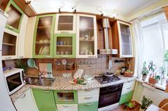 green kitchen interior with many utensils and window, fisheye view - stock photo