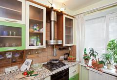 part of green kitchen interior with many utensils and window - stock photo