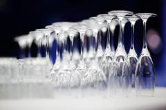 upturned set of wine glasses on blurred blue background - stock photo