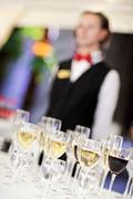 set of wine glasses with waiter on blurred background - stock photo