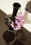 vase with orchid flower on brown shelf - stock photo