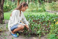 Young woman with hoe working in the garden bed Stock Photos