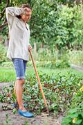 Tired young woman with hoe working in the garden bed Stock Photos