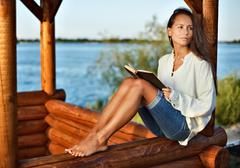 Young pensive lady with book in summerhouse on sunset Stock Photos
