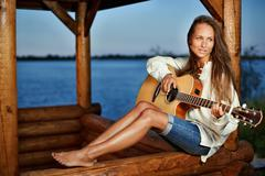 Young woman playing guitar in summerhouse on sunset Stock Photos