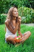 beautiful woman eating pear on the green grass - stock photo