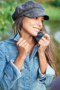attractive young woman dressed in jean jacket and beret - stock photo